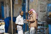Men read newspaper at the street in Sanaa, Yemen.
