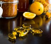 Yellow vitamin capsules, on background lemon, honey and spices