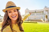 picture of piazza  - Portrait of happy young woman pointing on piazza venezia in rome italy  - JPG