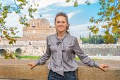 Portrait Of Happy Young Woman On Embankment Near Castel Sant'angelo In Rome Italy