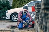 Cheerful Workman Laying Paving Bricks In Winter