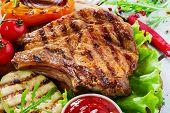 stock photo of pork chop  - Grilled Pork Chops  on bone with vegetables on a wooden surface - JPG