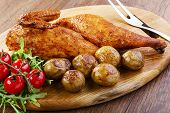 half baked chicken with new potatoes on the board