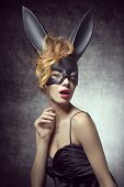 foto of bunny costume  - Beautiful sexy charming woman in carnival black costume of bunny with wild hairstyle and red lips - JPG