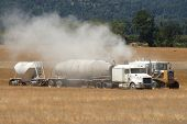 foto of spreader  - Large semi truck loads up a big tire agricultural spreader with lime - JPG