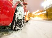 pic of stud  - Studded tyre of red car on street in winter evening - JPG