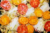 stock photo of flabby  - Raw chiken on baking tray with tomato and potato - JPG