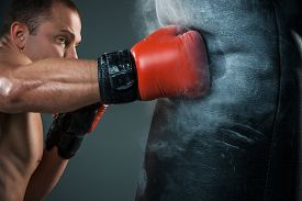 foto of boxers  - Young boxer in red gloves boxing over black background
