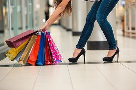 foto of heavy bag  - Woman legs with shopping bags against the backdrop of a shopping center - JPG