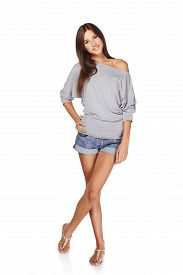 foto of short legs  - Full length of smiling young slim tanned female in denim shorts standing with crossed legs - JPG