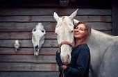 pic of horse face  - Young woman and her cremello horse on the background of horse and deer skulls - JPG