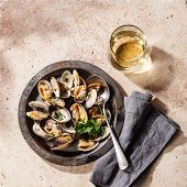 stock photo of clam  - Shells vongole venus clams in metal dish and wine on stone background - JPG