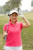 foto of ladies golf  - Cheerful Asian golf player with a club looking at the camera - JPG