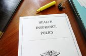 foto of insurance-policy  - Health Insurance Policy on an office desk - JPG
