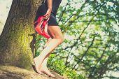 foto of barefoot  - Barefoot brunette girl outdoor with red high heels in her hands - JPG