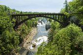 image of hydro  - Scenic view of Rainbow Falls and of the suspended Arch Bridge in Ausable Chasm town of Keeseville in Upstate New York - JPG