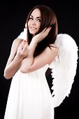 stock photo of ero  - Happy young angel with a candle over black background - JPG
