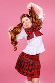 image of up-skirt  - Cute smiling teen girl in school plaid skirt and white blouse posing over pink background - JPG
