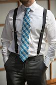 picture of suspenders  - A young man with his hands in his pockets wearing suspenders and a colorful blue teal patterened tie - JPG