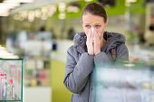 image of blowing  - Young woman blowing her nose while in a modern pharmacy - JPG