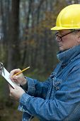 picture of hard_hat  - contractor handyman builder smiling confident happy on the job writing estimate - JPG