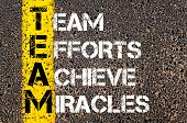 stock photo of miracle  - Concept image of Business Acronym TEAM as TEAM EFFORTS ACHIEVE MIRACLES written over road marking yellow paint line - JPG