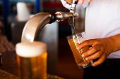 stock photo of draft  - Draft beer pour in a glass from the crane - JPG