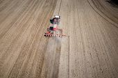 stock photo of cultivator-harrow  - Aerial view of the the tractor harrowing the large brown field in spring season - JPG
