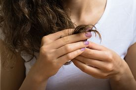 foto of split ends  - Female hand of a young girl holding the ends of her curly hair - JPG