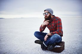 stock photo of hobo  - beard lumbersexual hipster sitting on suitcase in deep thought - JPG