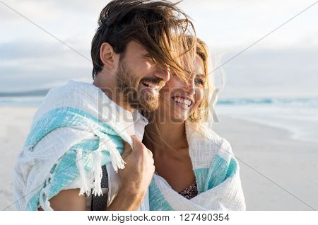 Happy couple wrapped up in blanket at beach. Young couple wrapped in towel on beach. Smiling couple