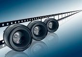 Lens & Film Strip On Blue Background