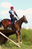 horseman jumps an obstacle having lost stirrups
