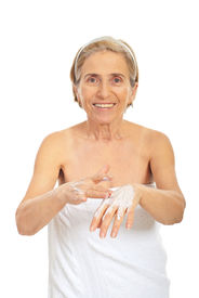 pic of beautiful senior woman  - Smiling senior woman applying cream on her hands isolated on white background - JPG