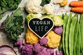 a heart-shaped signboard with the text vegan life placed on a pile of some different raw vegetables, poster