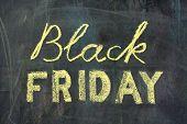 Black Friday Yellow Advert Against Chalkboard On Desk poster