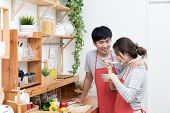 Happy Asian Young Couple Make Cooking In Kitchen, Man Looking And Smilling To Woman, Wife Preparing  poster
