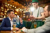 Celebrating St. Patricks Day In Cafe: Two Friends Wearing Suits Sitting At Table And Making Order Wh poster