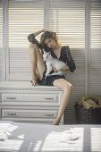 Young Woman With Baby Sheep On Chest Of Drawers. Girl Cuddle Small Lamb In Bedroom. Love, Care Conce poster