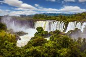 The waterfalls Iguazu. World of falling water. Picturesque basaltic ledges form the famous waterfalls. The concept of active and exotic tourism