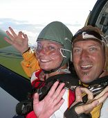 Two Skydivers Waving From An Aeroplane Doorway Before Skydiving