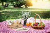Picnic Lunch Meal Outdoors Park Food Concept, Closeup Of Picnic Basket With Drinks, Food And Flowers poster