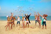 Beach wedding of happy newlywed couple around their friends