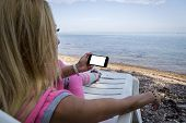 Girl Sitting And Resting On A Beach Chaise Lounge And Having Fun With Her Phone. Beautiful Blue Sky  poster