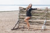 Adorable Slim Young Female Model Stands On Beach Near Wooden Hence, Demonstrates Slender Legs, Recre poster