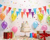 Birthday cake on a table against a wall with decoration flags and balloons poster
