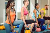 Full length of three young and beautiful determined people holding kettlebells while exercising Russ poster