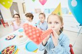 Little girl with birthday whistle having fun by birthday table with her friends and teacher behind poster