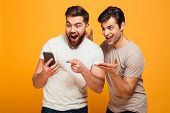 Portrait of a two cheerful young men looking at mobile phone isolated over yellow background poster