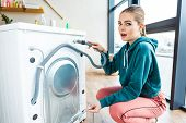 Shocked Young Woman Looking At Camera While Crouching Near Broken Washing Machine poster